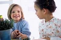 Two children with herbs in kitchen