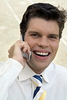 Smiling young man on cell phone, close-up