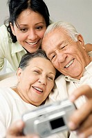 Woman and her senior parents taking picture with digital camera, close-up