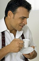 Side profile of a man holding a cup and saucer