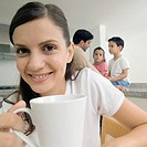 Close-up of smiling young woman holding coffee cup with man and two children in background