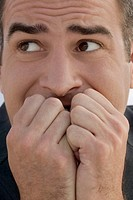 Worried businessman with hands covering mouth, close-up
