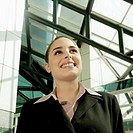 Smiling businesswoman standing under skylight and looking up