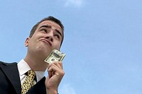 Businessman outdoors holding one hundred dollar bill, low angle view, close-up