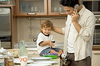 Side profile of a man talking on a mobile phone with a baby sitting on the counter