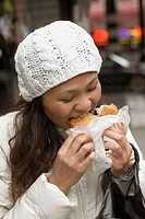Thai (Asian) woman eating, dressed for winter in NYC. USA