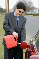Man filling gas using a container on roadside