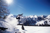 Skier jumping mid air, side view