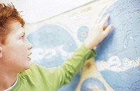 Boy (10-11) looking at world map