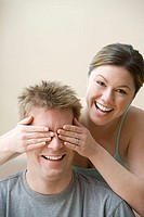 Woman covering husband´s eyes