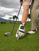 Man placing golf ball on tee