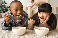 Boy and girl lying in living room eating cereal