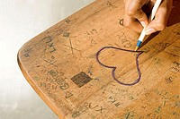 Student drawing a heart on her desk
