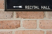Recital hall sign on brick wall