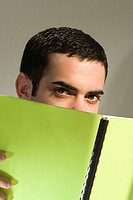 Male student hiding behind a book