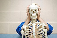Male student stood behind human skeleton
