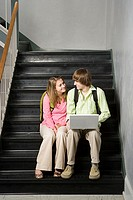 Teenage couple sat on school stairway