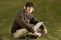Male student using a laptop outdoors