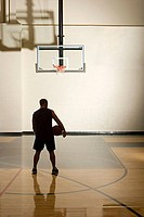 Basketball player alone in basketball court (thumbnail)