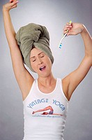 Young woman age 20-25, wearing a 'Vintage Yoga' printed novelty t shirt tank of white cotton.  She is stretching and yawning while holding tooth brush...