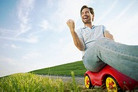 Man riding a child´s toy car