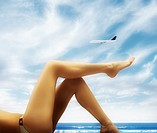 Woman's legs on tropical beach as airplane flies by