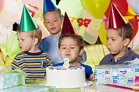 Boy blowing out birthday candles at party with friends