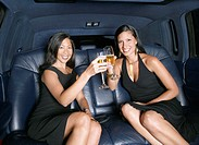 Portrait of two women toasting with champagne in backseat of car