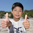 Young boy making thumbs up sign