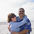 Tourist couple hugging on the beach