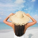 Woman wearing a straw hat on the beach