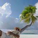 Man relaxing on a palm tree at the beach (thumbnail)