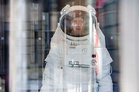 Astronaut looking at the camera from behind glass