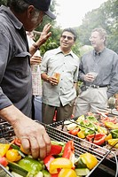 Middle-aged men grilling vegetables