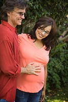 Middle aged man touching his wife's pregnant belly (thumbnail)