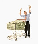 Businessman pushing shopping cart full of money