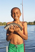 Young boy holding a freshly-caught fish