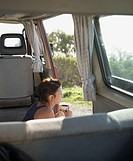 Woman drinking coffee in the back of a van