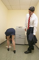 Businessman admiring female colleague's buttocks as she bends over