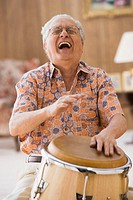 Older man drumming on a bongo