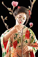 Asian woman in ethnic clothes arranging flowers