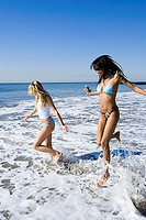 Profile of two young women running in the water on the beach (thumbnail)