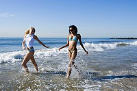 Two young women running in the water on the beach (thumbnail)