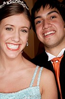 Teenage couple smiling for the camera in formal wear