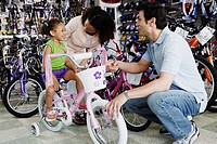 Parents helping young daughter with bike in bike shop