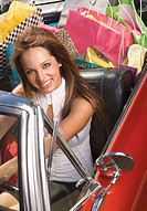 Portrait of woman sitting in convertible stuffed with shopping bags