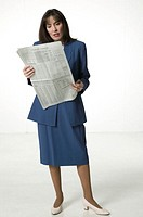 Businesswoman standing reading newspaper