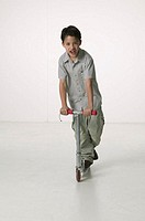 Boy (8-9) riding on scooter in empty room
