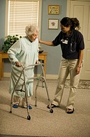 Physiotherapist helping senior woman with walker in retirement home