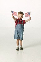 Boy (3-4), waving American flags, posing in studio, portrait